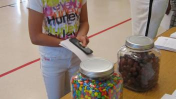 Children counting candy in a jar.