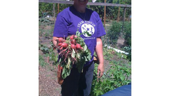 Mary, the garden coordinator, shows off radishes that participants harvested