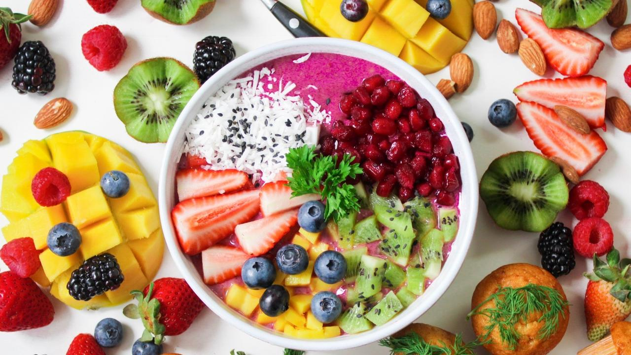 a smoothie bowl with fresh fruit, almonds, and muffins