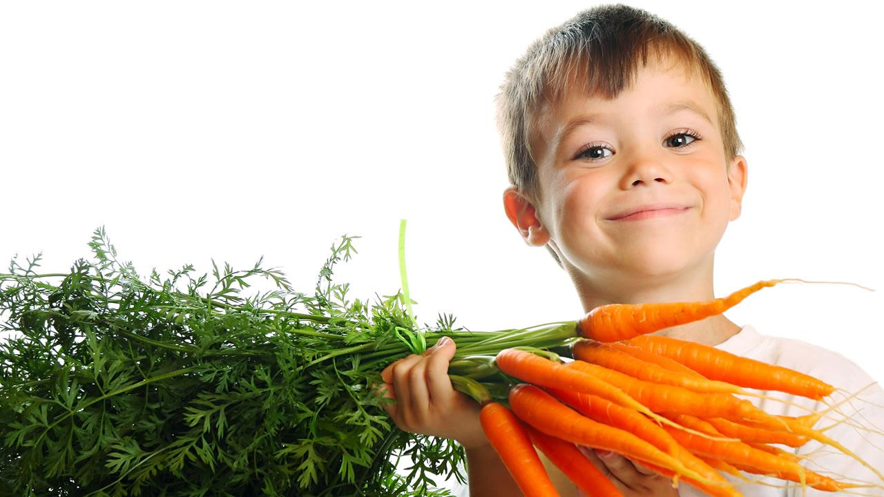 Child holding up carrots.