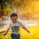 boy running through sprinkler