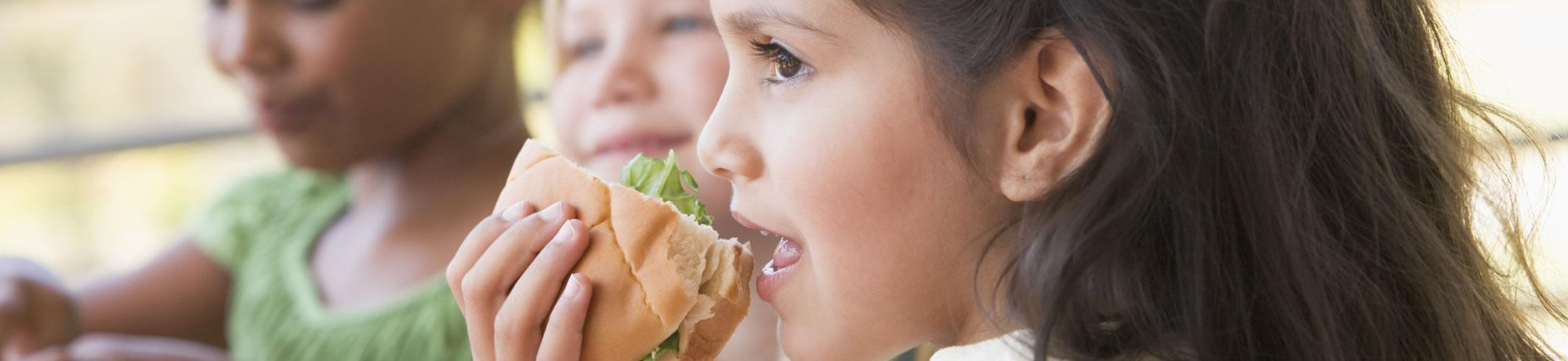 Girl eating a sandwhich.